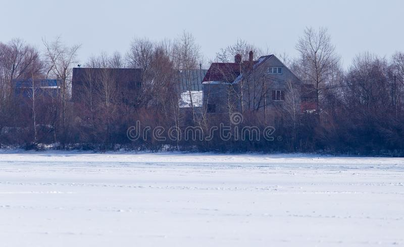 Chambre près d'un lac congelé dans le village en hiver images libres de droits