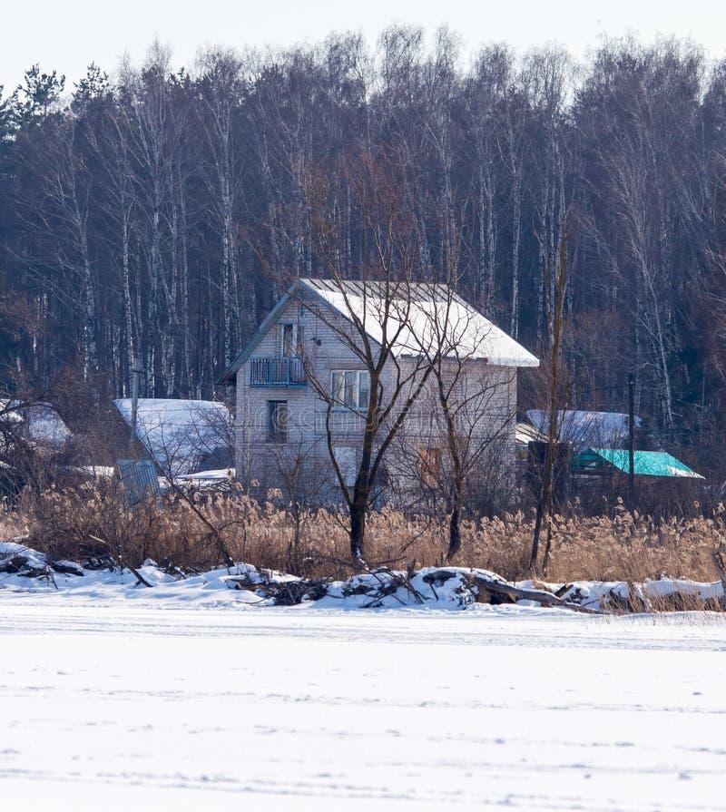 Chambre près d'un lac congelé dans le village en hiver photo stock