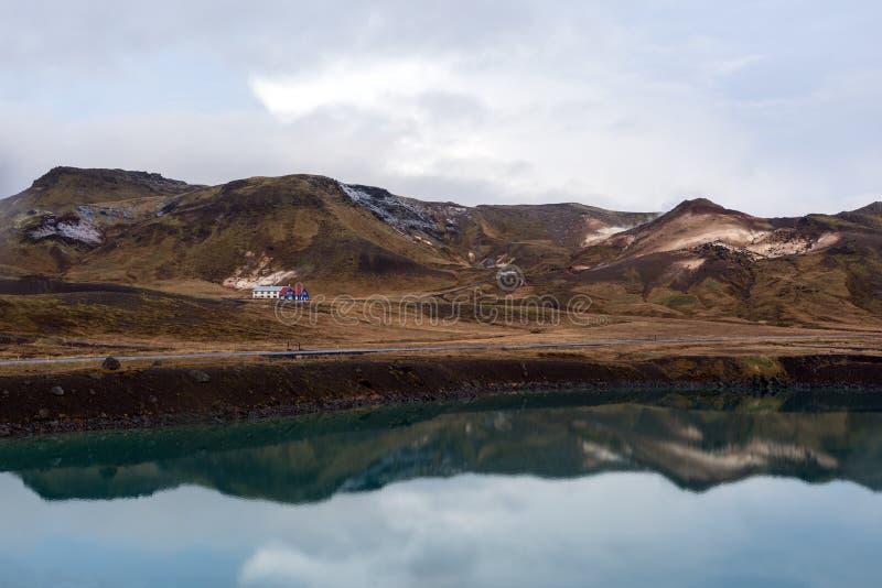 Chambre près du lac dans le paysage abandonné en Islande, à l'arrière-plan d'une montagne neigeuse image stock