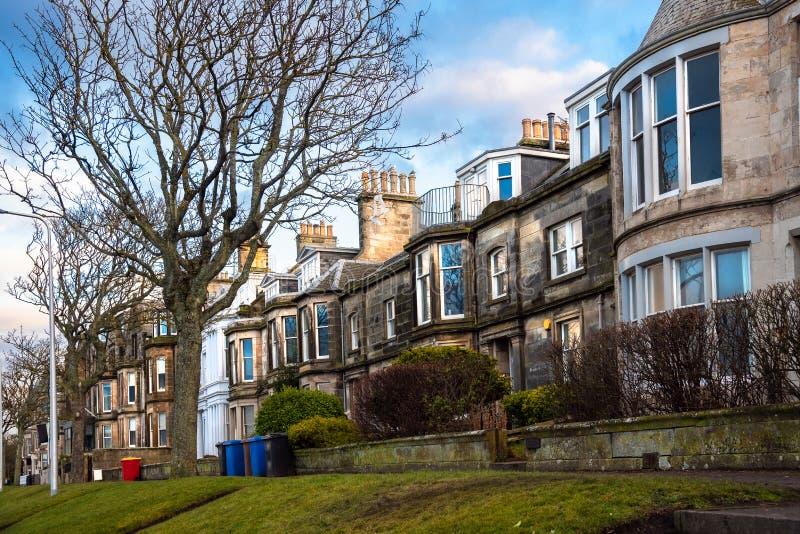 Chambres en terrasse britanniques traditionnelles le long d'un trottoir rayé par arbre images stock