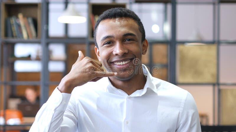 Chame-me sinal pelo homem negro no escritório fotografia de stock royalty free