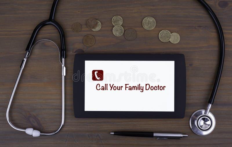 Chame seu médico de família Text no dispositivo da tabuleta em uma tabela de madeira imagens de stock royalty free