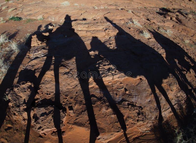 Chameaux d'équitation avec des ombres dans le désert photographie stock libre de droits