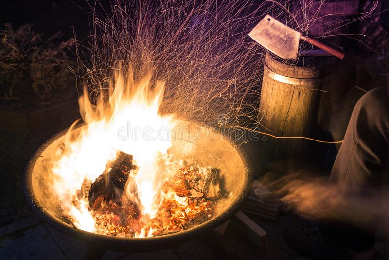 Chaminé ardente com lote de sparkles brilhantes na noite A fogueira flamejante com machado e os povos pequenos arrasta no fundo foto de stock royalty free