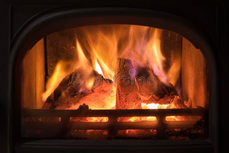Chaminé ardente com os logs de madeira que queimam-se para dentro Luz morna, r imagens de stock