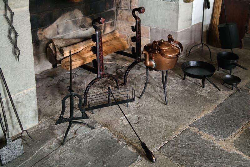 Chaminé de pedra do vintage com ferramentas do metal e madeira do fogo imagens de stock