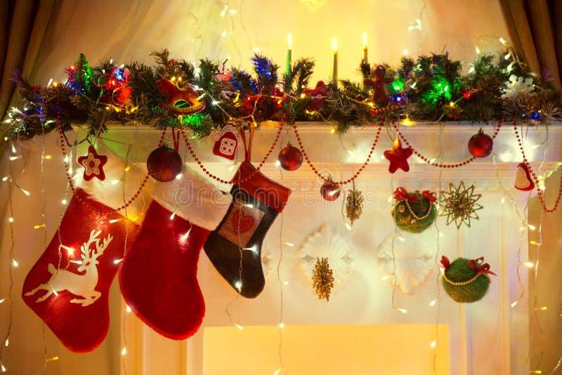 A chaminé do Natal, peúgas de suspensão da família, Xmas ilumina Decoratio fotografia de stock royalty free