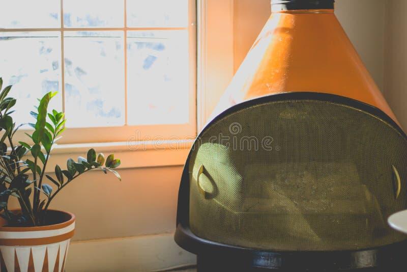 Chaminé moderna alaranjada em uma sala minimalistic com a grande janela de vidro e uma planta fotografia de stock