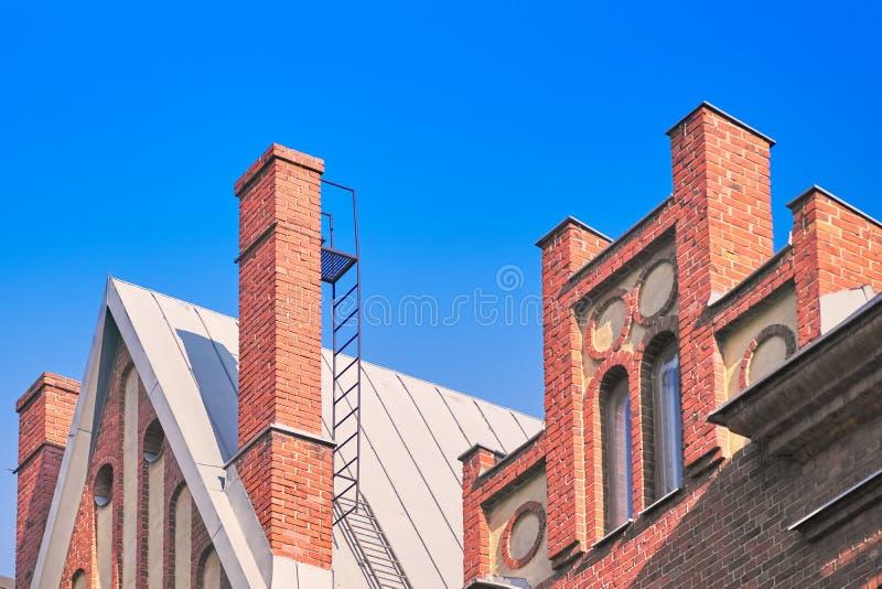Chaminé no telhado, fragmento do tijolo vermelho da fachada de uma construção de tijolo contra o céu azul foto de stock royalty free