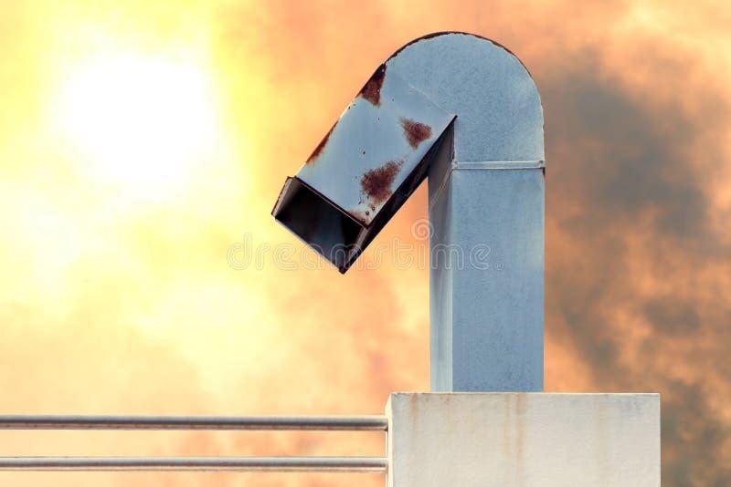 A chaminé, o conduto, a chaminé da fábrica industrial na poluição alaranjada do céu e o sol iluminam-se imagens de stock royalty free