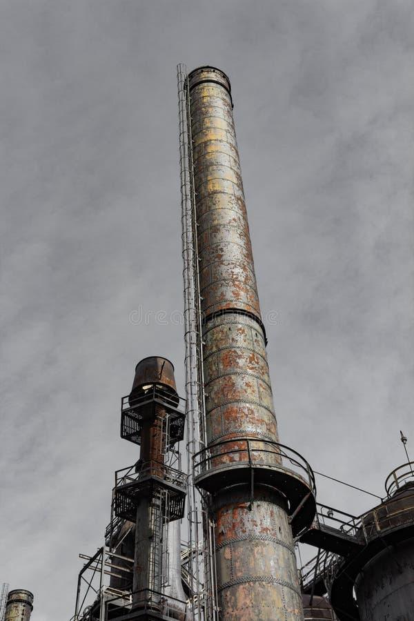 Chaminé oxidada e rebitada centrada contra o céu nublado cinzento foto de stock