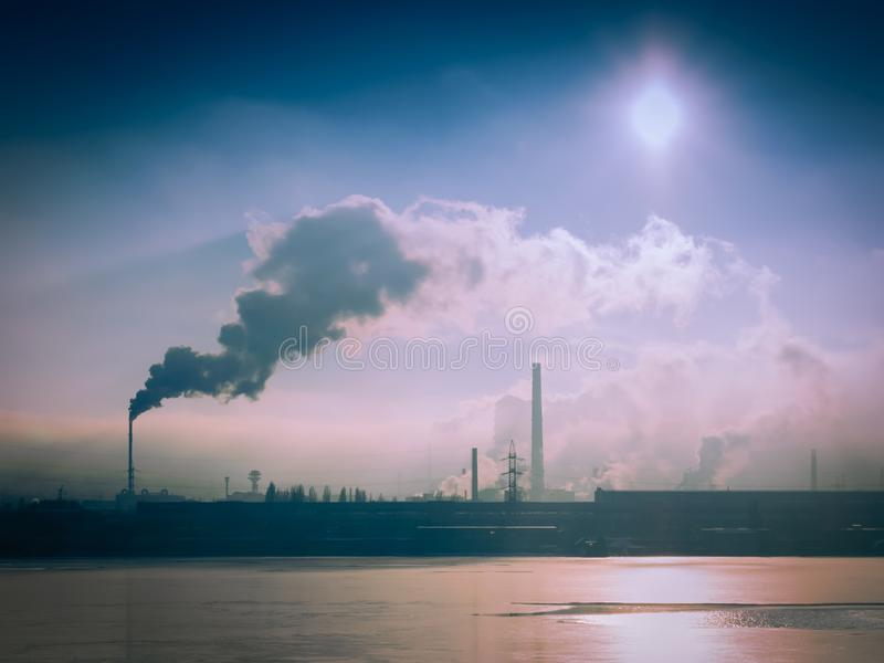 Chaminés de fumo da planta de aço perto do rio no dia ensolarado do inverno fotos de stock