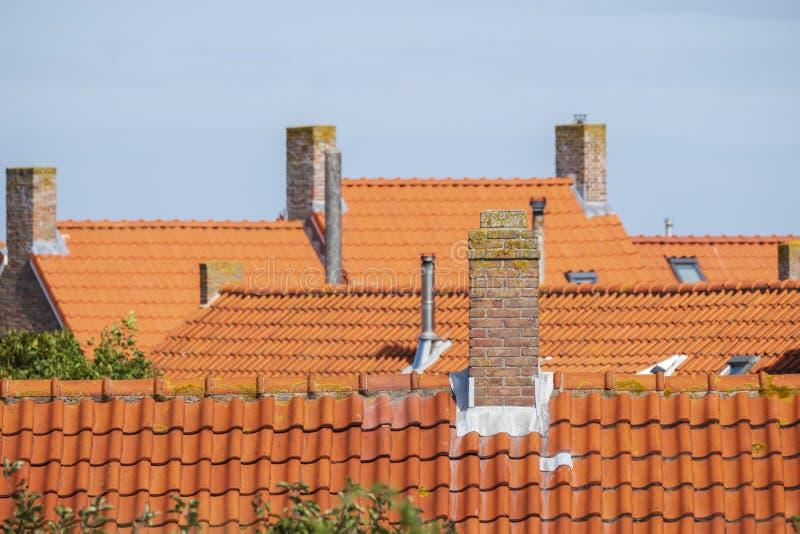 Chaminés de pedra nos telhados com as telhas de telhado alaranjadas fotografia de stock royalty free