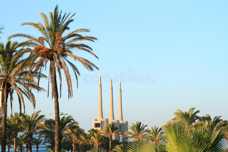 Chaminés do central elétrica do ciclo combinado do ² s de Besà atrás dos palmtrees fotos de stock royalty free