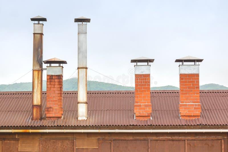 Chaminés do tijolo e tubulações da ventilação da lata no telhado de uma cabana de madeira em um fundo de montes verdes em um dia  imagem de stock royalty free