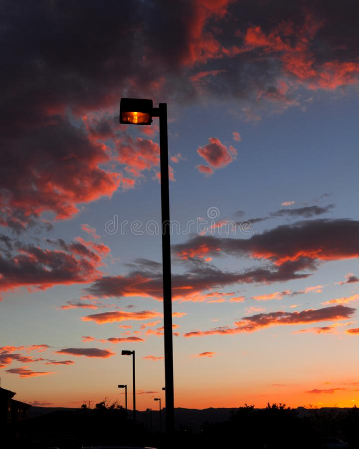 The chaming sunset sky. The light just turn along the road and the sun is falling. the clouds became red orange with blue sky stock photography
