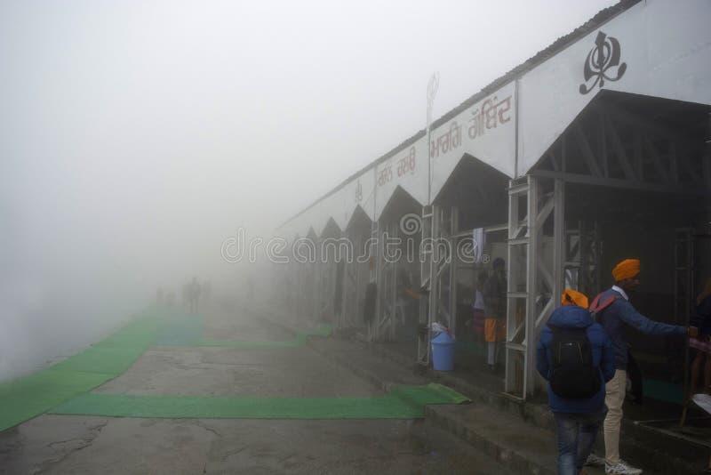 CHAMOLI-OMRÅDE, UTTARAKHAND, INDIEN, Juni 2018, turist och besökare på Hemkund Sahib under dimmig morgon arkivbild