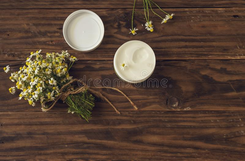 Chamomile bouquet and fragrant body cream on a wooden table royalty free stock image