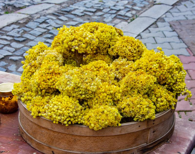 A chamomile bundles in the wooden basket on the table on the street prepared for selling stock photos