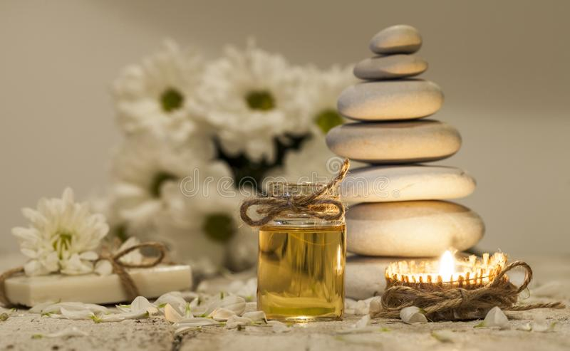 Chamomile essential oil, bouquet of chamomile flowers, stack of rocks and candle stock images