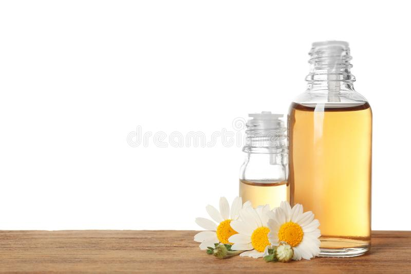 Chamomile flowers and cosmetic bottles of essential oil on wooden table against white background stock image
