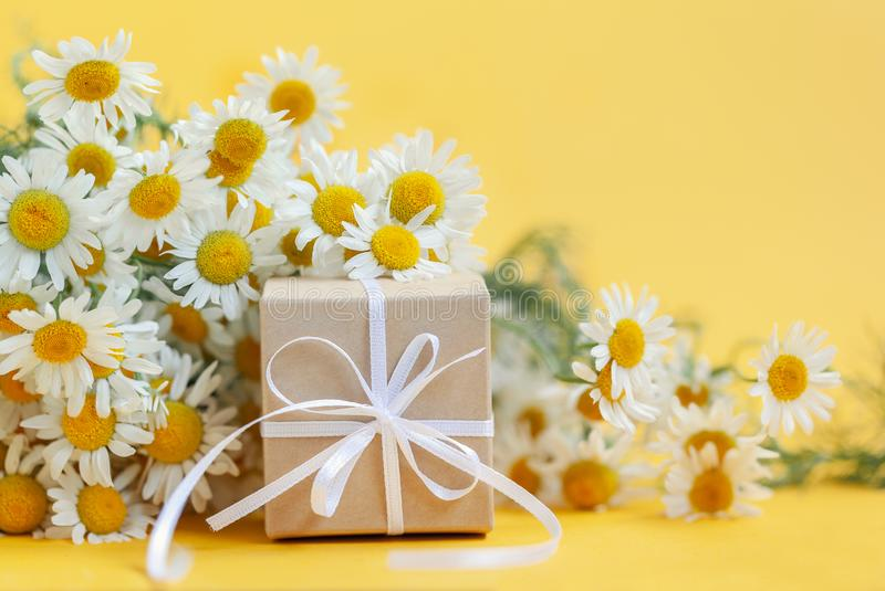 Chamomile flowers and gift or present box on yellow background. Holiday celebration concept stock photography
