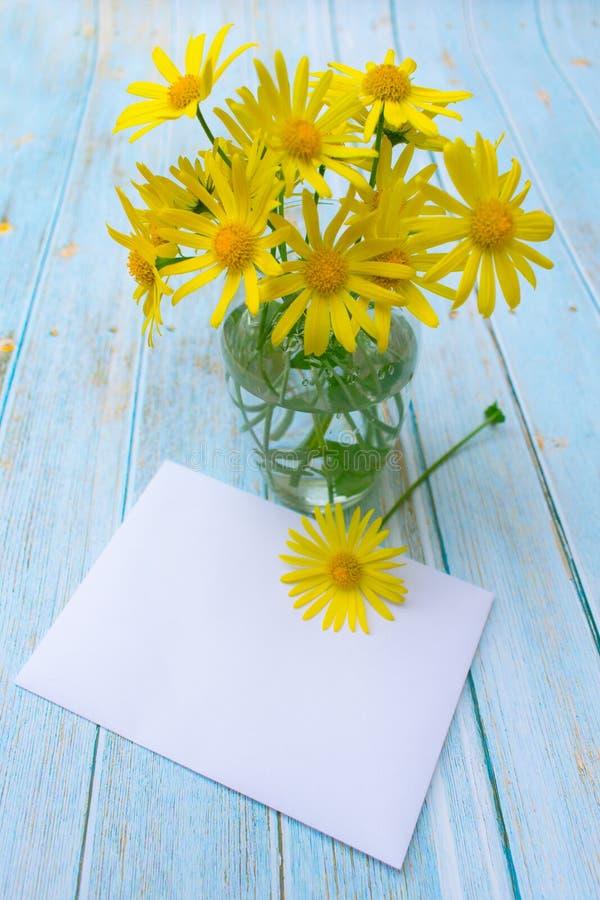 Chamomile kwitnie w wazie i kopercie na stole pocztówka, wiadomość, zaproszenie obrazy stock