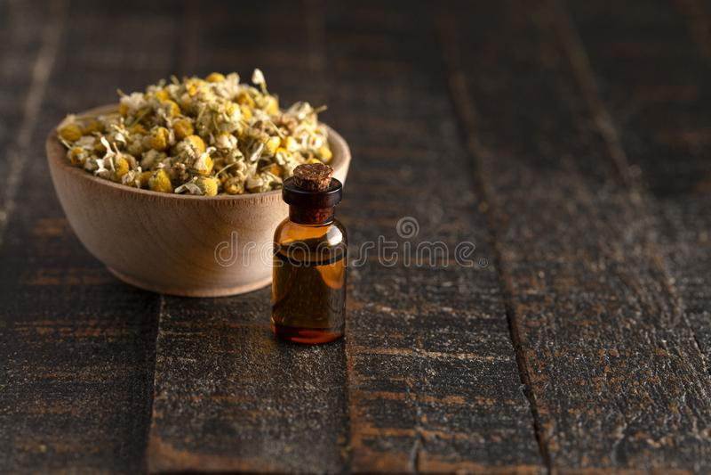 Chamomile olej z Wysuszonym Chamomile Kwitnie na Drewnianym stole zdjęcia stock
