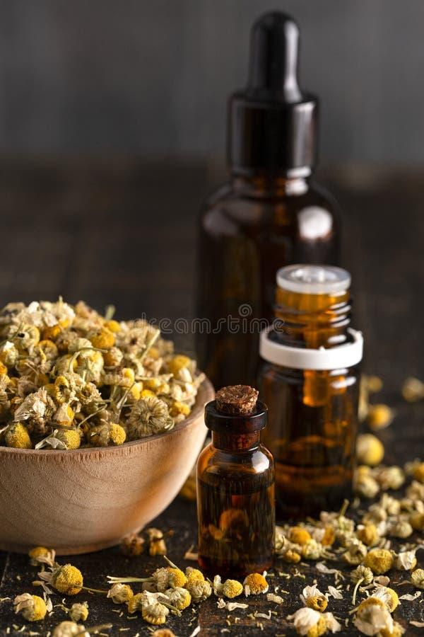 Chamomile olej z Wysuszonym Chamomile Kwitnie na Drewnianym stole zdjęcie royalty free