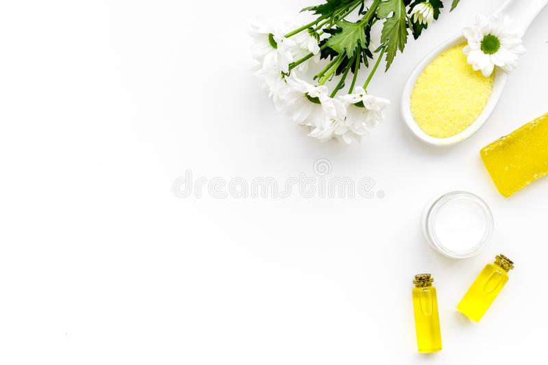 Chamomile spa cosmetics with natural herbal ingredients. Chamomile spa salt, soap, oil and cream on white background top stock images