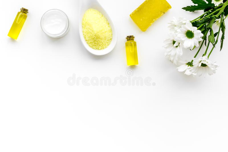 Chamomile spa cosmetics with natural herbal ingredients. Chamomile spa salt, soap, oil and cream on white background top stock image