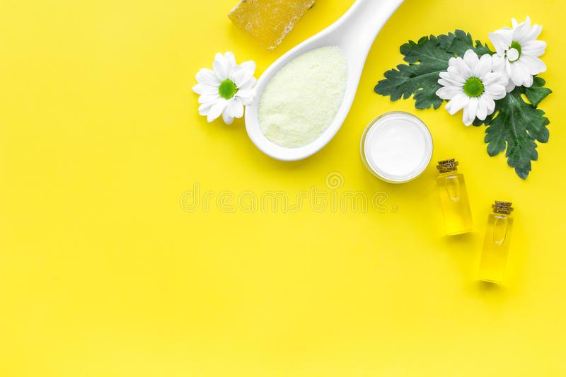 Chamomile spa cosmetics with natural herbal ingredients. Chamomile spa salt, soap, oil and cream on yellow background royalty free stock images