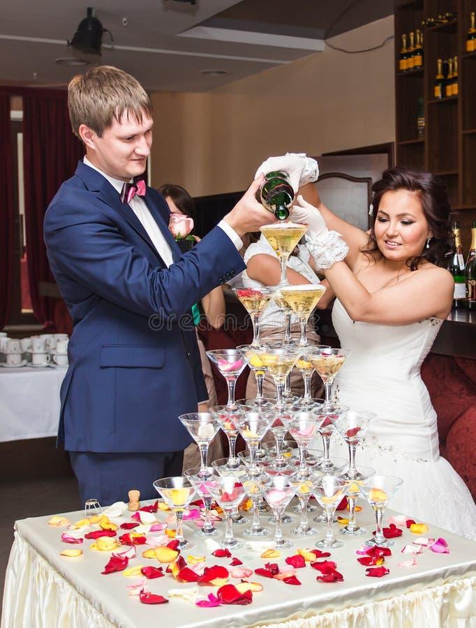 Champán de colada de novia y del novio en el vidrio Pirámide del champán imagenes de archivo