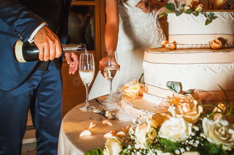 Champán de colada del novio en vidrios cerca de un pastel de bodas imagenes de archivo