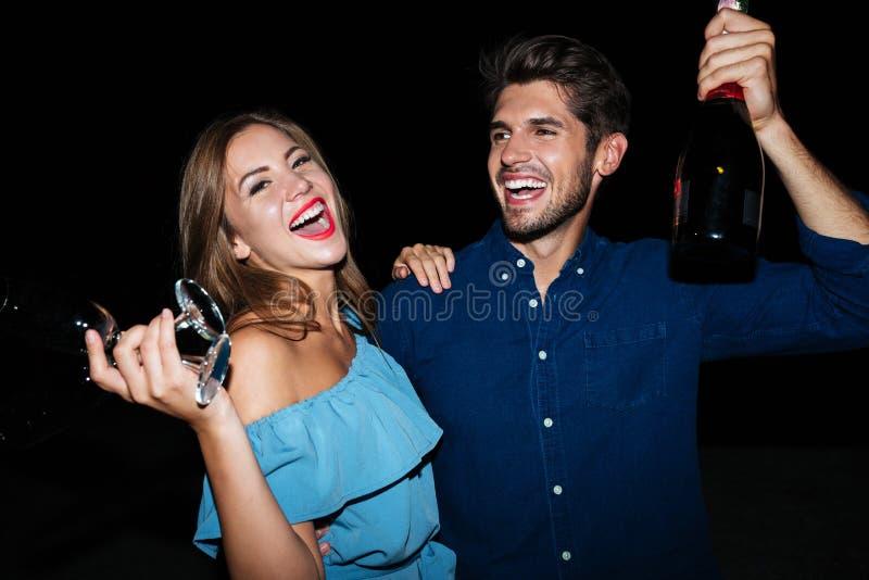 Champán de consumición de los pares jovenes felices y noche el reírse imagen de archivo libre de regalías