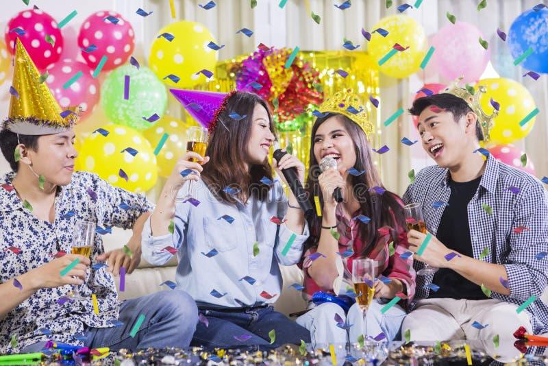 Champán de consumición feliz de la gente joven en el partido fotos de archivo