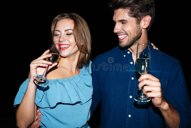 Champán de consumición sonriente de los pares jovenes hermosos en la noche junto foto de archivo libre de regalías