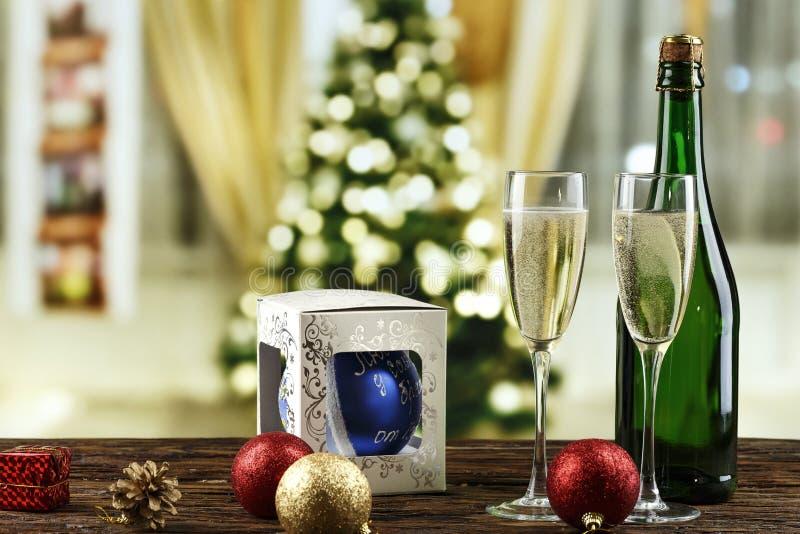 Champán en vidrios y en una botella y juguetes en el árbol de navidad en el fondo del bokeh imagen de archivo
