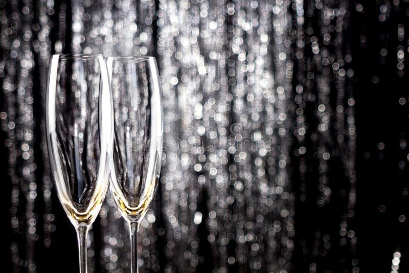 Champán o copas de vino vacío con la decoración de la malla de la Navidad del brillo en fondo imagen de archivo