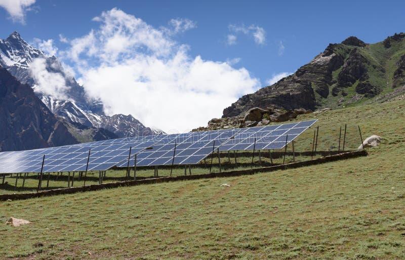 Champ avec des rangées des panneaux solaires bleus dans la prairie avec le fond de crête de neige au Jammu-Cachemire, Inde photographie stock libre de droits
