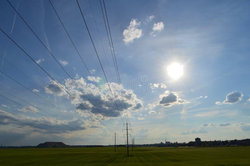 Champ avec le ciel ensoleillé, lignes électriques photos stock