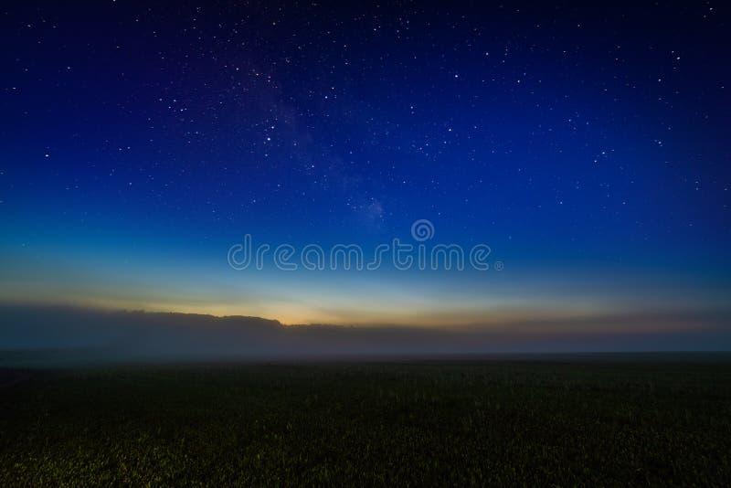 Champ brumeux de nuit avec le gradient étoilé de ciel nocturne et d'horizon de postluminescence photographie stock libre de droits