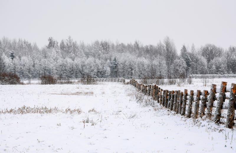 champ couvert de neige dans la campagne Une barrière en bois des terres cultivables photos stock