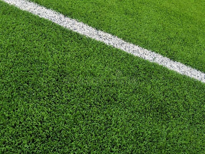 Champ d'herbe artificiel avec la ligne blanche fond photo stock