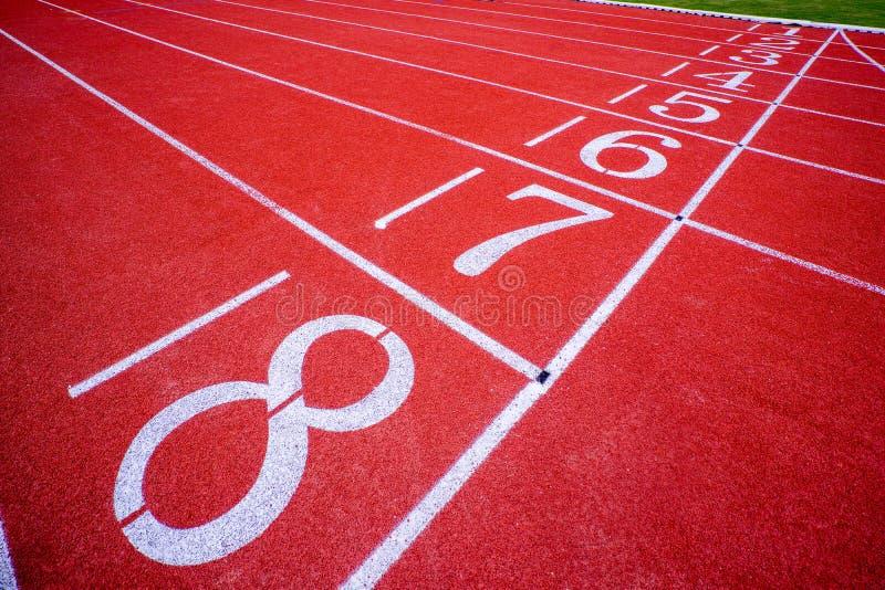 Champ de courses courant extérieur rouge avec les lignes blanches et le nombre dedans  photo stock