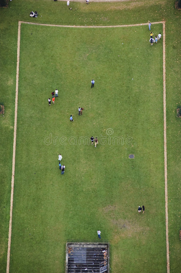 Champ de Mars. View of section of Champ de Mars from top of Eiffel Tower showing grassy field with tourists walking on rectangular shaped area stock photo