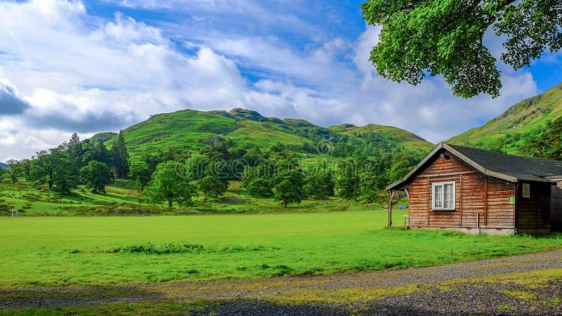 Champ et montagne verts avec la maison urbaine au R-U photos stock