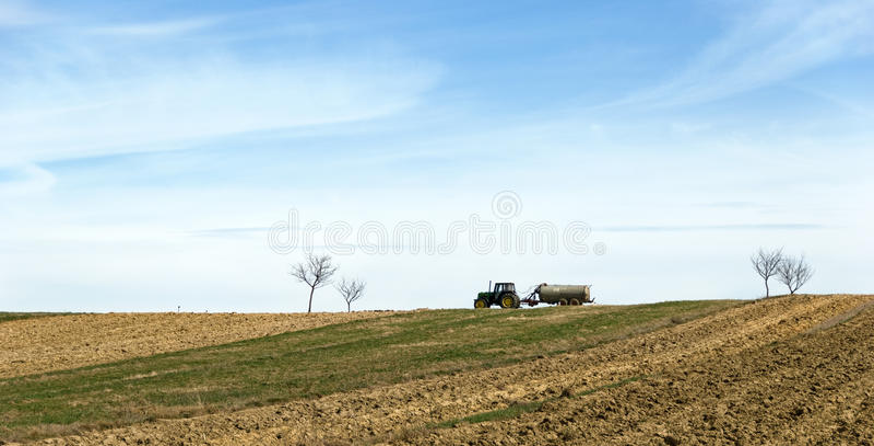 Champ labouré avec l'écarteur de tracteur et d'engrais de liquide image libre de droits