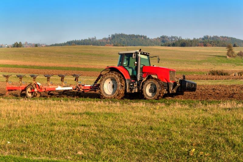 Champ rouge de poteau de tracteur Travaux sur le terrain d'automne La vie à la ferme Paysage agricole dans la République Tchèque photographie stock libre de droits