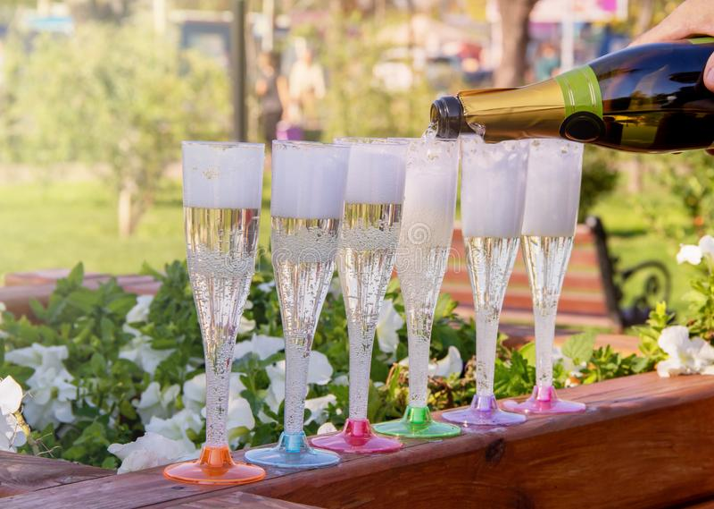 Champagne è versata da una bottiglia nei vetri multicolori in mezzo ad un parco un giorno soleggiato fotografie stock